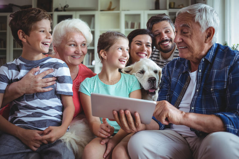 Happy multi-generation family using digital tablet in living room stock photos