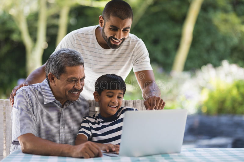 Happy multi-generation family using laptop at porch stock photo