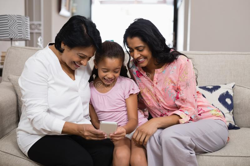 Happy multi-generation family using mobile phone together at home stock photo