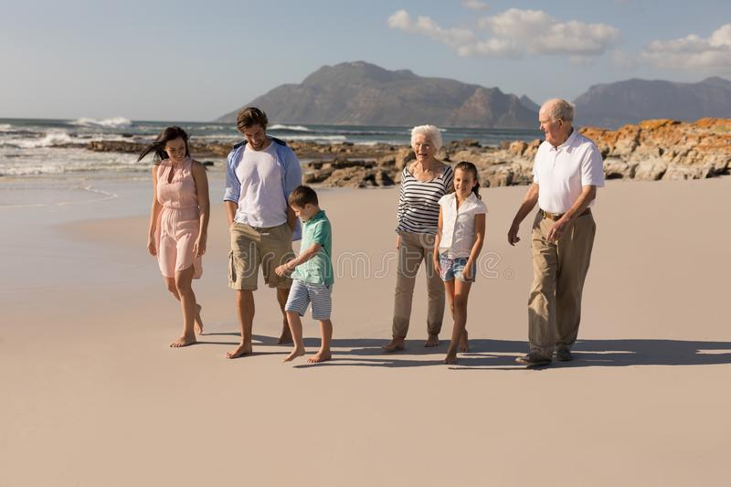 Happy multi-generation family walking and having fun on beach. Front view of happy multi-generation family walking and having fun on beach in the sunshine stock images