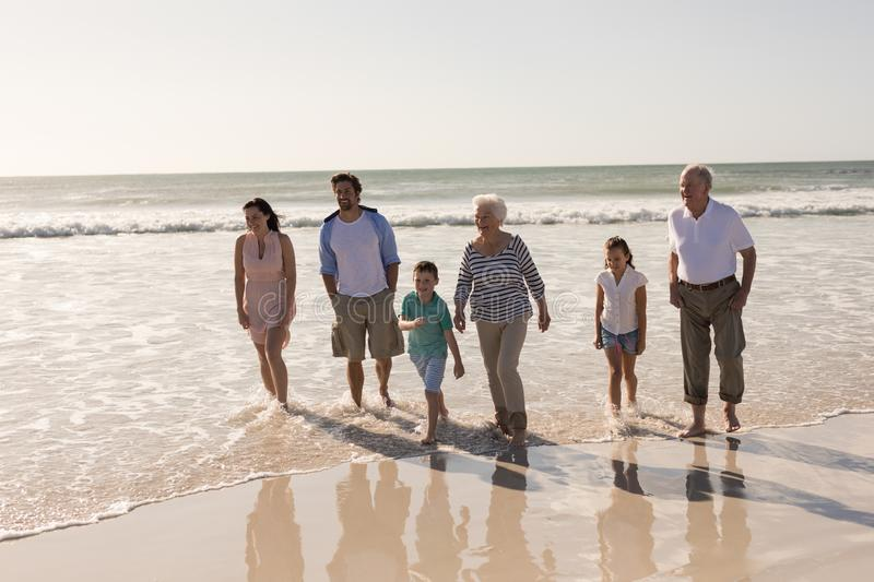 Happy multi-generation family walking and having fun on beach. Front view of happy multi-generation family walking and having fun on beach in the sunshine stock photos