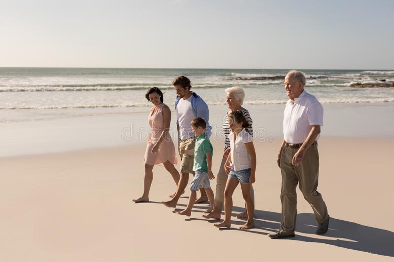 Happy multi-generation family walking and having fun on beach. Side view of happy multi-generation family walking and having fun on beach in the sunshine royalty free stock photography