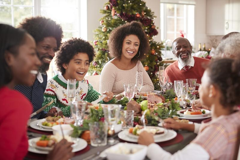 Happy multi generation mixed race family sitting at their Christmas dinner table eating and talking, selective focus stock image