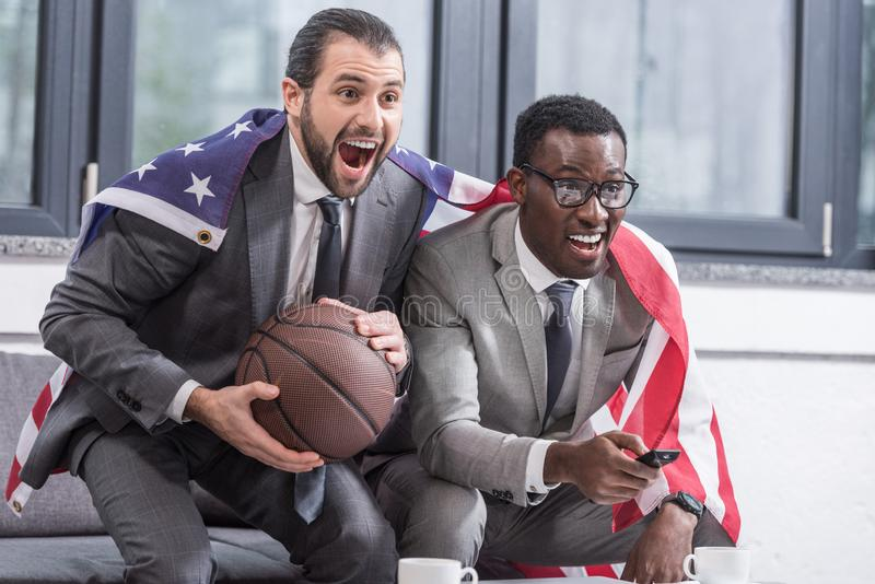 happy multicultural business partners with american flag watching basketball match royalty free stock photo