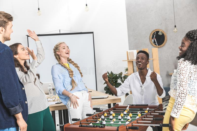 happy multicultural colleagues celebration win while playing table football stock photos