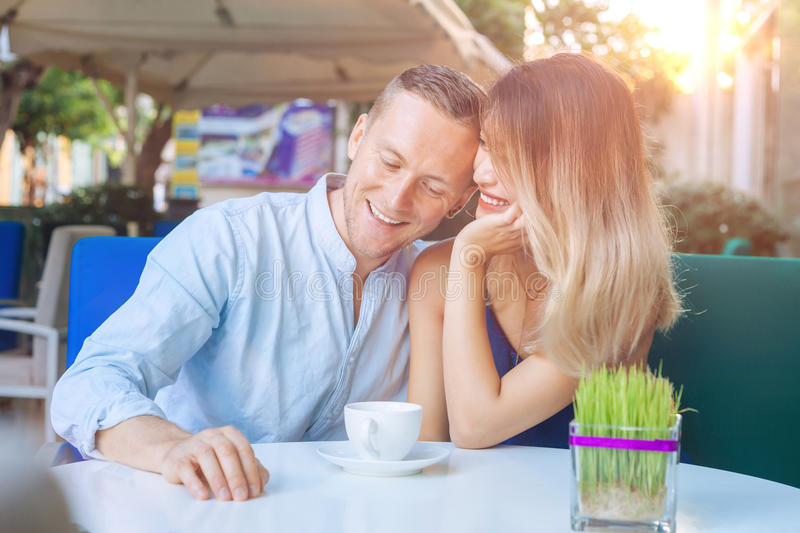 Happy multicultural couple smiling drinking coffee royalty free stock photography