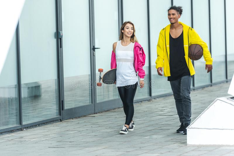 happy multicultural couple walking with skateboard and basketball ball stock photo