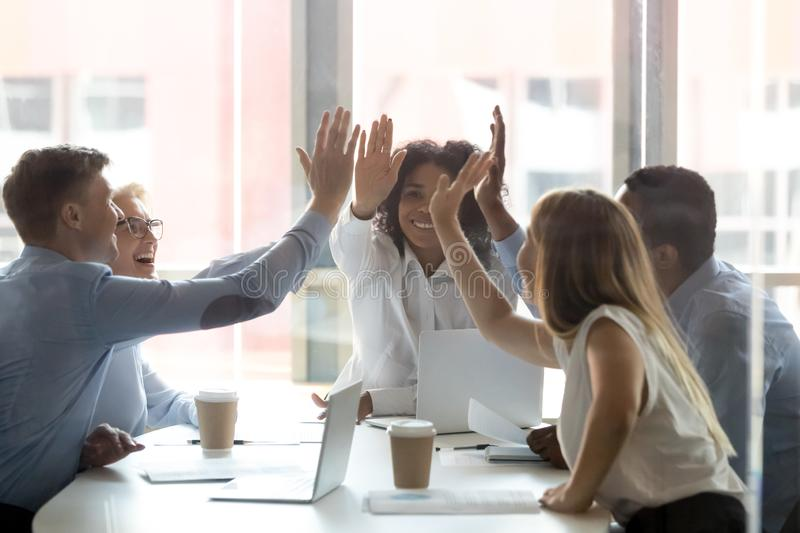 Happy multicultural executive team people give high five celebrate success stock photography