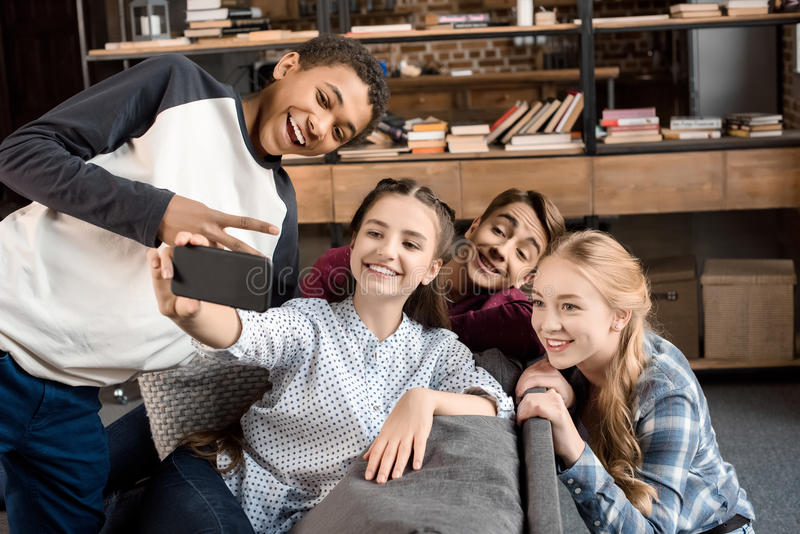 Happy multicultural teenagers group taking selfie on smartphone and sitting on sofa at home stock images