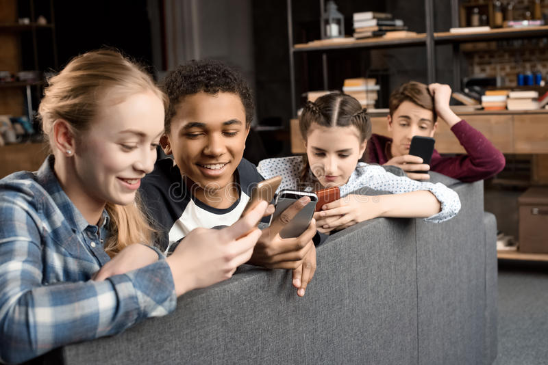 Happy multicultural teenagers group using smartphones and sitting on sofa at home royalty free stock image