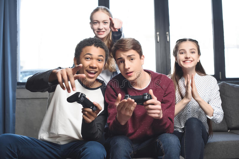 Happy multicultural teenagers playing video games with joysticks at home stock image