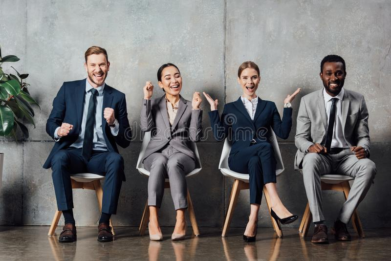 Happy multiethnic businesspeople sitting on chairs and cheering with clenched fists in stock photos