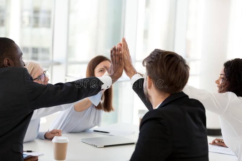 Happy multiethnic colleagues give high five for motivation royalty free stock images
