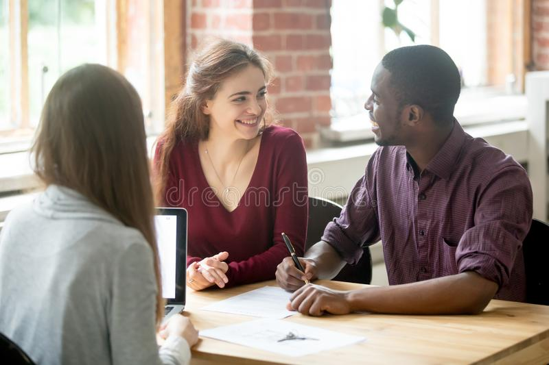 Happy multiethnic couple looking at each other before signing co. Ntract in front of female real estate agent. African american men holding pen, preparing to royalty free stock photo