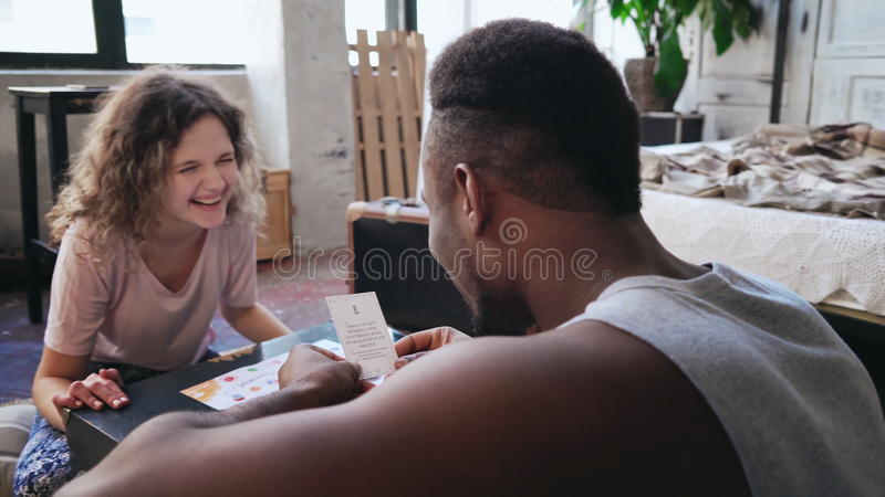 Happy multiethnic couple in pajamas playing the board game on the floor. Man throws dice and puts the card, woman laugh. royalty free stock photos