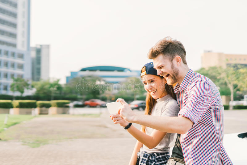 Happy multiethnic couple taking selfie during sunset in the city, fun and smiling, love or gadget technology concept.  stock photography