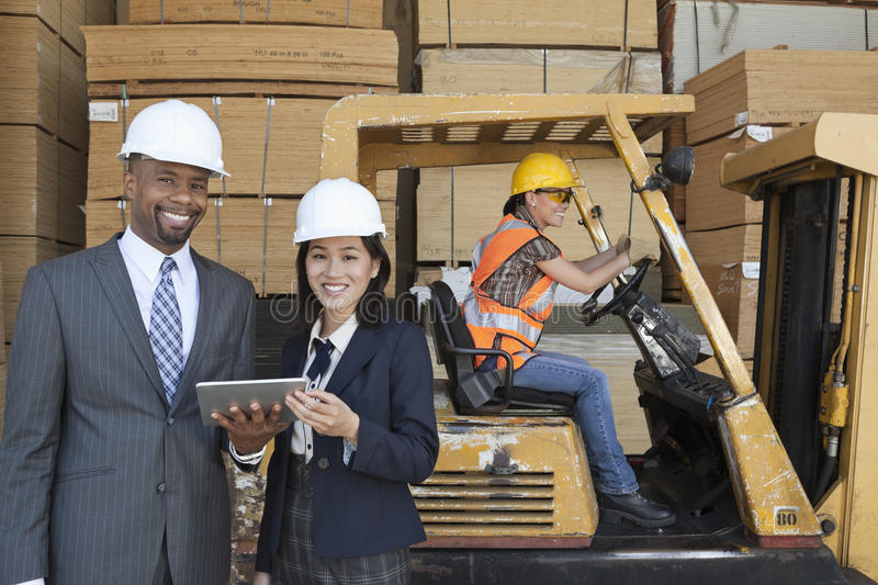 Happy multiethnic engineers holding tablet PC with female worker driving forklift truck in background royalty free stock photography