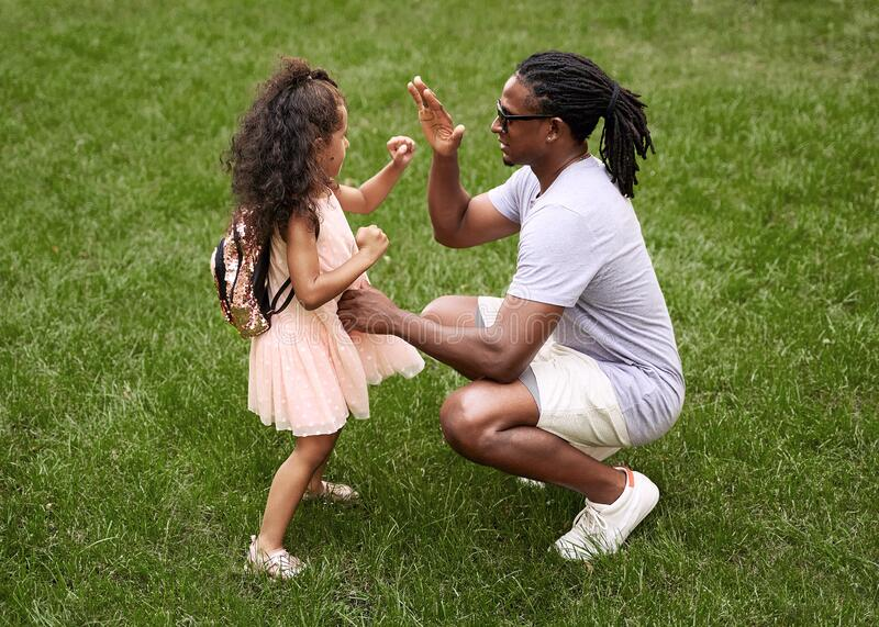 Happy multiethnic family. Fit black father teaching his adorable cute mixed race daughter in pink dress how to fight on stock photography