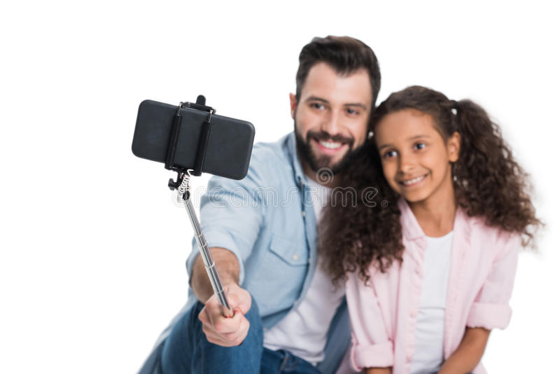 Happy multiethnic father and daughter taking selfie while sitting together stock photo