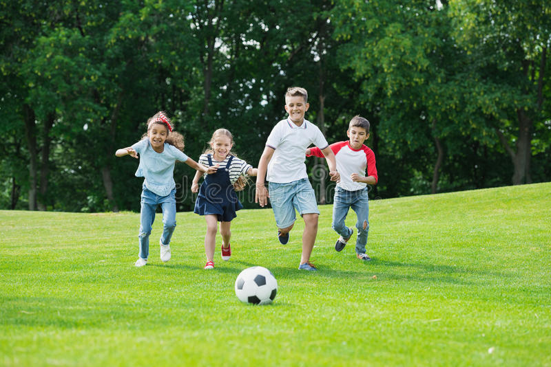 Happy multiethnic kids playing soccer with ball in park royalty free stock photo