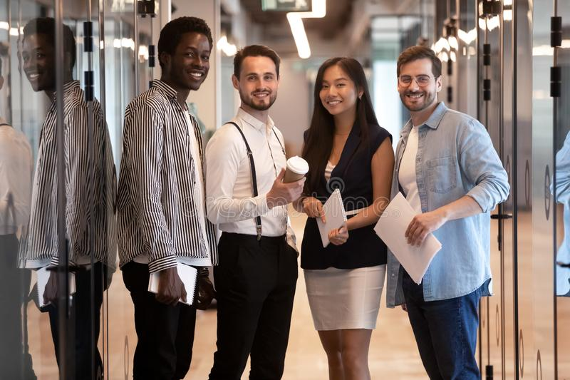 Happy multiethnic professional business team standing together in office hallway royalty free stock photo