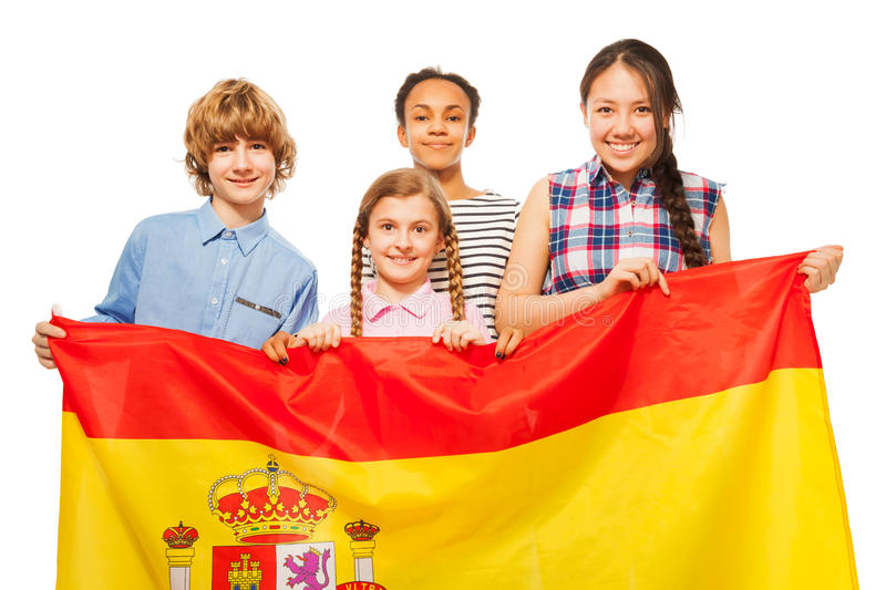 Happy multiethnic teenage kids with flag of Spain. Group of four happy multiethnic teenage kids with flag of Spain, on white royalty free stock image