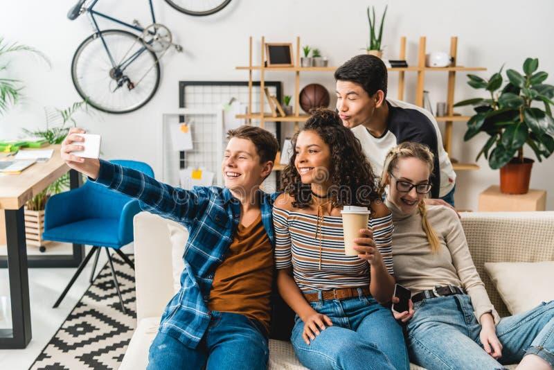 happy multiethnic teenagers sitting on sofa and taking selfie stock photo