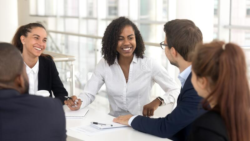 Smiling diverse employees discuss ideas brainstorming at office meeting stock photo