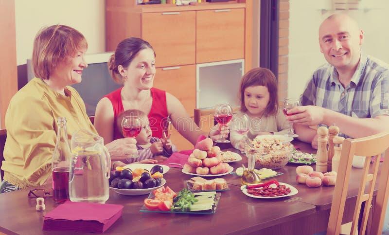 Happy multigeneration family around festive table. Happy multigeneration family together around festive table at home royalty free stock photo
