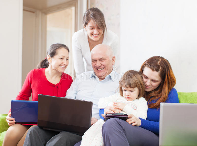 Happy multigeneration family uses few portable electronic communication devices stock photography