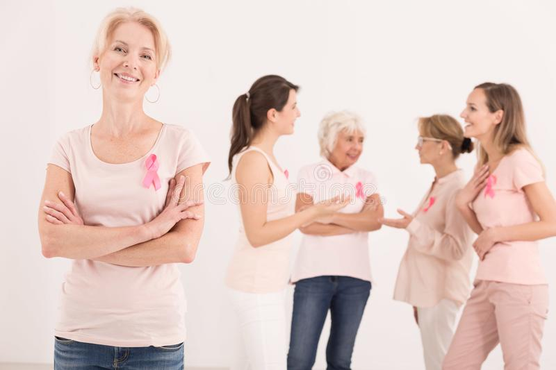 Happy multigenerational breast cancer survivors. Multigenerational support group for breast cancer survivors, happy smiling cancer survivor women with pink royalty free stock photos