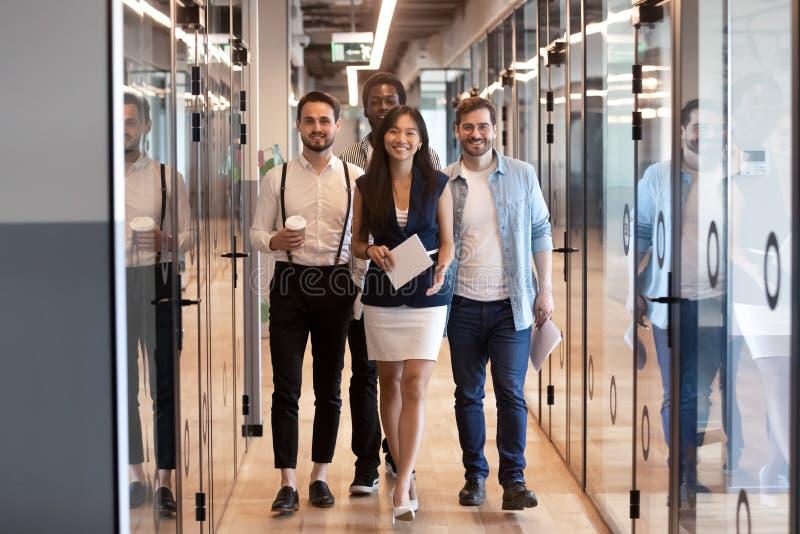 Happy multinational corporate business team stand in office hallway. Happy multinational corporate business team smiling confident multiethnic professional stock photos