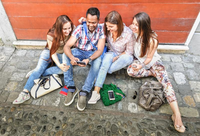 Happy multiracial best friends having fun using mobile smart phone royalty free stock image