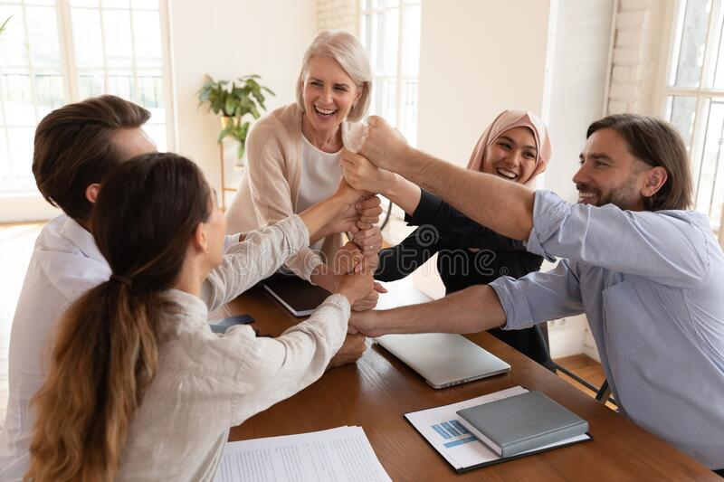 Happy multiracial colleagues stack fists engaged in teambuilding royalty free stock images