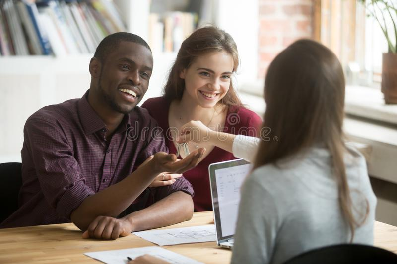 Happy multiracial couple getting keys to new home from realtor. Excited young customers buying real estate house concept, diverse family buyers purchasing royalty free stock images