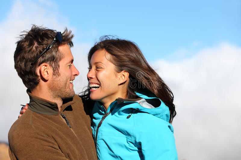 Happy multiracial couple laughing in autumn. Happy young couple smiling outdoors looking at each other with love. Active young couple portrait during hiking