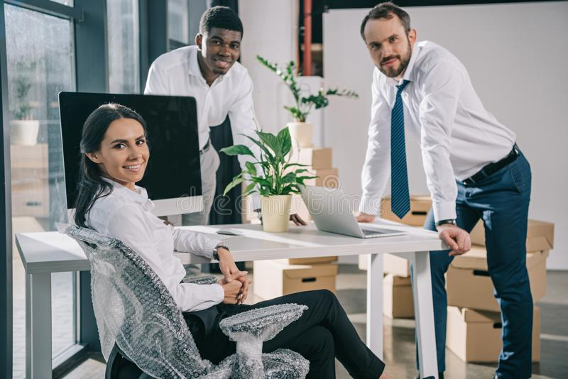 happy multiracial coworkers smiling at camera while moving in new stock photography