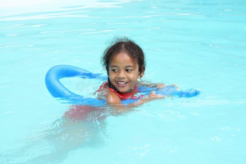 Happy multiracial ethnic girl child learning to swim stock photos