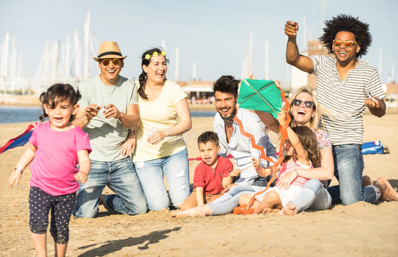 Happy multiracial families and children playing together with kite at beach vacation - Multicultural summer joy concept with royalty free stock photography