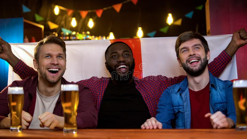 Happy multiracial fans supporting english representatives on song contest, flag royalty free stock photo