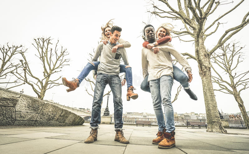 Happy multiracial friends couples having fun with piggiback. In winter time waiting spring - Friendship concept with multicultural young people with funny royalty free stock images