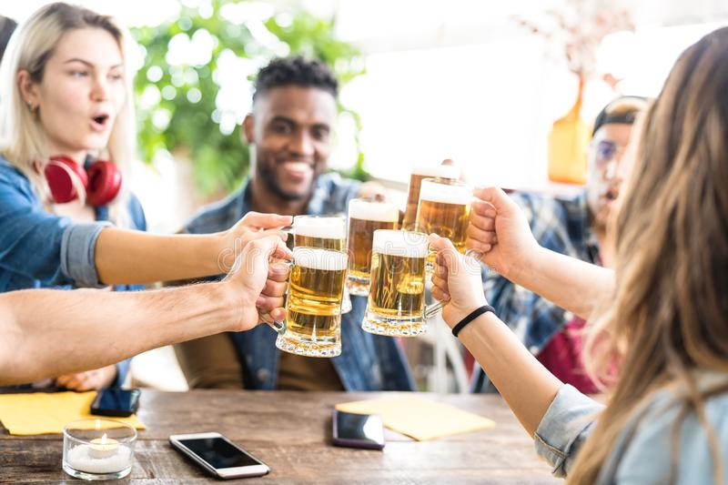 Happy multiracial friends drinking and toasting beer at brewery bar - Friendship concept with young people having fun together. At cool pub restaurant - Focus royalty free stock images