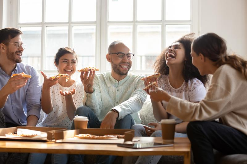 Happy multiracial friends enjoying home party time, eating pizza. stock images