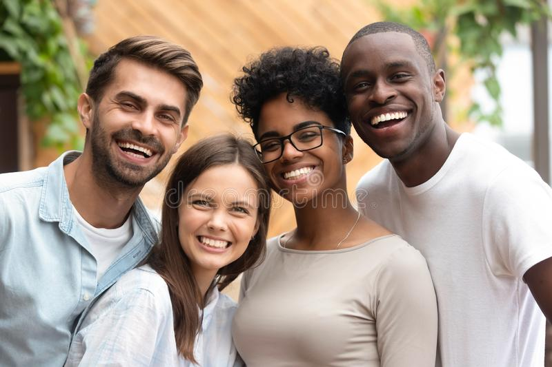 Happy multiracial friends group bonding looking at camera, portrait royalty free stock images