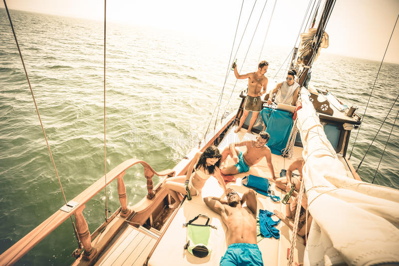 Happy multiracial friends having fun at sail boat trip party stock photos