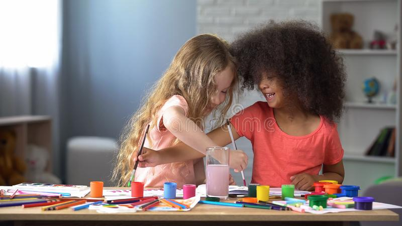 Happy multiracial friends painting with watercolors in kindergarten, hobby royalty free stock photography