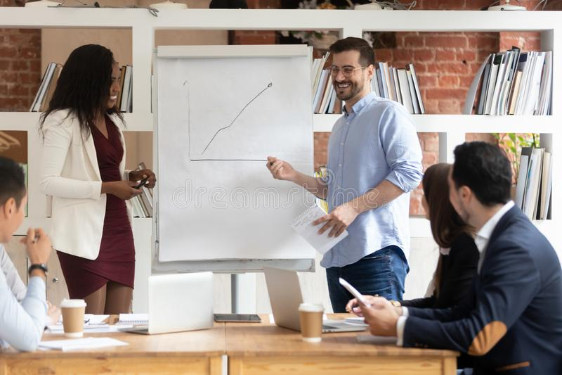 Smiling diverse presenters making whiteboard presentation at briefing royalty free stock images