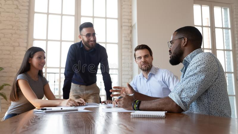Happy multiracial team listening african colleague at corporate briefing. Happy friendly multiracial business team people listening african colleague tell new royalty free stock photography