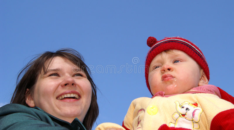 Happy mum with the child. Portrait of the happy mum with the child on a background of the dark blue sky royalty free stock images