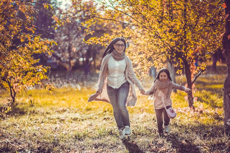 Happy mum and the daughter play autumn park royalty free stock images
